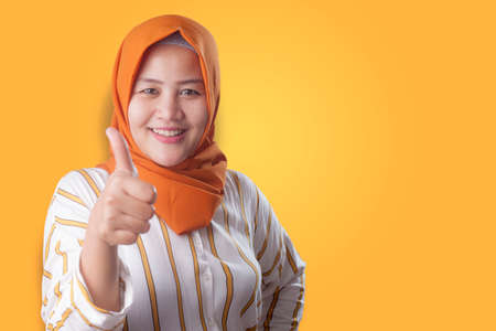 Portrait of young Asian muslim lady wearing hijab shows thumbs up gesture, smiling happy face, approved OK sign Banco de Imagens