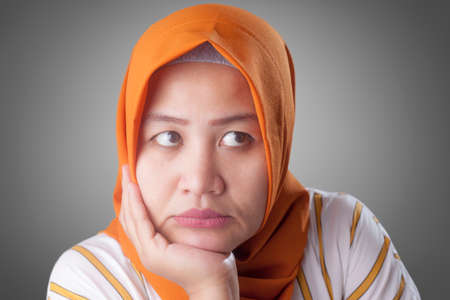 Asian muslim businesswomen wearing hijab with curiousity thinking expression. Looking for solution of a problem, hand under chin. Close up head and shoulders