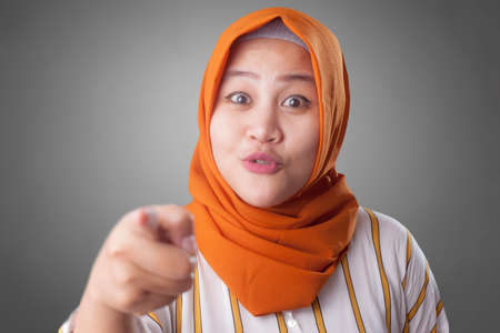 Portrait of cute beautiful Asian muslim lady smiling to camera and pointing forward as if choosing you concept