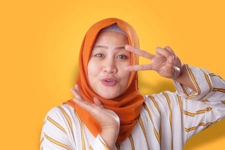 Portrait of happy beautiful young Asian muslim lady wearing hijab smiling and posing for camera against orange background