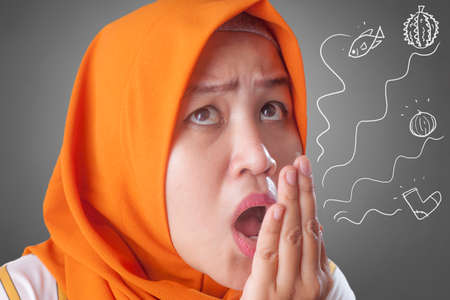 Portrait of cute funny Asian muslim lady wearing hijab check her own breath, mouth smell odor Stock Photo