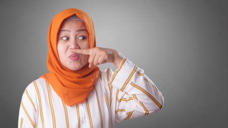 Portrait of cute funny Asian muslim lady wearing hijab close her nose because of bad disgusting smell odor Stok Fotoğraf
