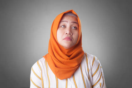 Young Asian muslim businesswoman wearing hijab looked tired, dizzy expression. Close up head and shoulders Reklamní fotografie