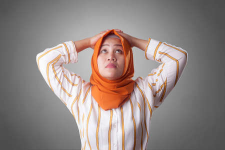 Asian muslim businesswomen wearing hijab with curiousity thinking expression. Looking for solution of a problem, hands behind head. Close up head and shoulders