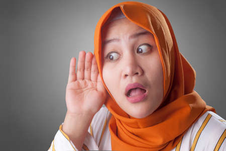 Portrait of Asian muslim lady wearing hijab hold her hand on ear trying to listening carefully to the conversation of someone, shocked curious facial expression Banco de Imagens