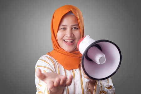 Portrait of Asian muslim woman calling or offering something with megaphone, advertising marketing concept