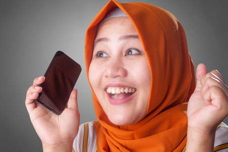 Portrait of young Asian muslim woman get good news on her phone, happy surprised expression