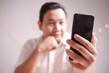 Close up image of businessman holding and using smart phone with selective focus Banco de Imagens
