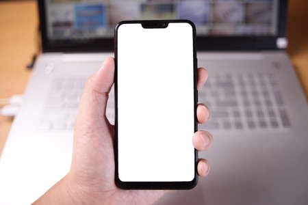 Close up image of smart phone mockup, businessman holding phone with white screen template