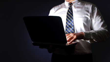 Businessman typing on laptop in the dark, executive manager working secretly concept Stockfoto