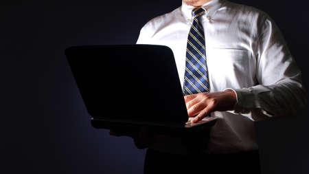 Uomo d'affari che digita sul computer portatile al buio, manager esecutivo che lavora segretamente concept Archivio Fotografico