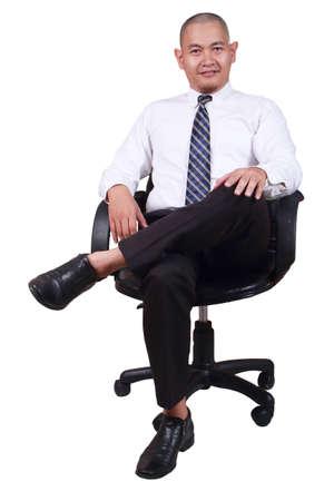 Felice giovane uomo d'affari asiatico di successo che sorride mentre è seduto su una sedia, isolato su bianco