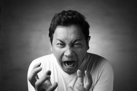 Young Asian man wearing white shirt shouting because of anger. Close up head and shoulders, monochrome black white image Reklamní fotografie