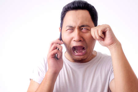 Young Asian man crying shocked worried expression by the phone. Over white background