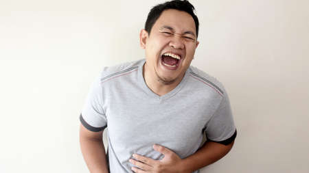 Portrait of funny young Asian man laughing hard with big open mouth, over grey background