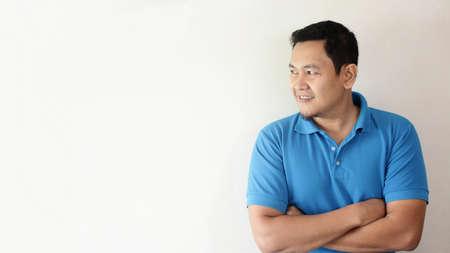 Portrait d'image photo d'un jeune homme asiatique mignon et attrayant souriant joyeusement, les bras croisés regardant sur le côté Banque d'images