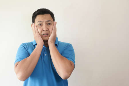 Portrait of young funny Asian man shocked or surprised expression with mouth open, worried to see something bad happen