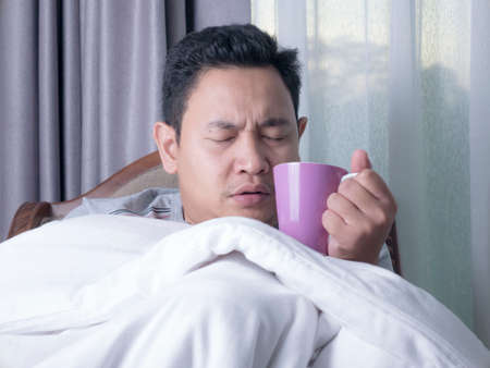 Sick cold young Asian man covered with blanket while sitting on chair, drinking hot drink