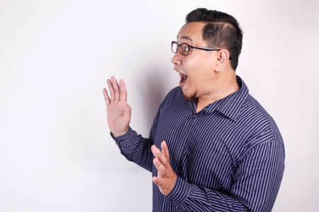 Portrait of young Asian man shocked to see something on his side, excited gesture with copy space