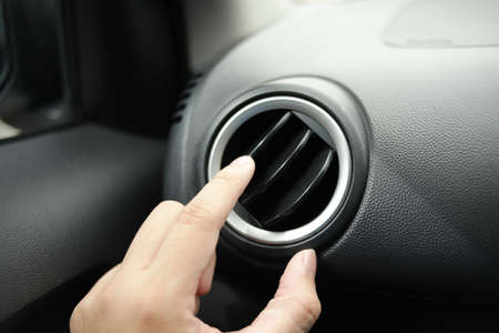 Close up image of adrivers hand adjusting air conditioner using the air conditioning tuner and the grid vent fin in car