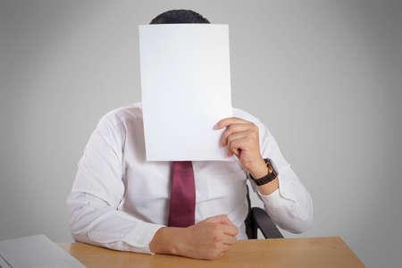 Porträt des Geschäftsmannes, der sein Gesicht mit leerem leerem Papier bedeckt. Kopieren Sie das Raummodell für eine anonyme Person