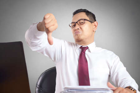 Angry Asian boss manager businessman shows thumb down gesture, upset disappointed gesture