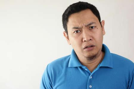 Porträt eines jungen asiatischen Mannes, der skeptisch, unzufrieden oder misstrauisch aussieht und sich auf die Kamera freut Standard-Bild