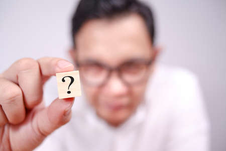 Close up image of businessman showing wooden block with question mark on it, selective focus