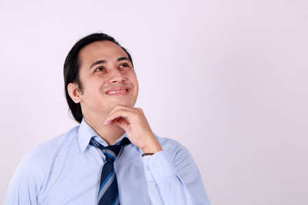 Photo image of young Asian man looked happy thinking and looking up, having good idea. Half body portrait against white wall with copy space Reklamní fotografie