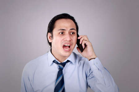 Young Asian man with long hair shocked worried expression by the phone. Over Grunge Grey Background