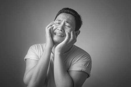 Immagine fotografica di un uomo asiatico divertente che piange forte, triste depressione frustrazione espressione senza speranza, immagine monocromatica in bianco e nero