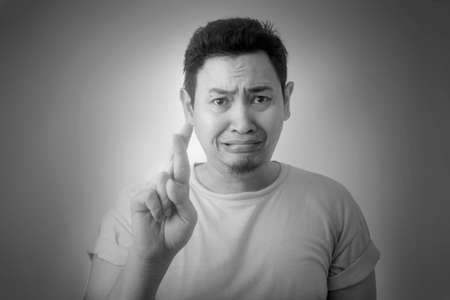 Portrait of sad young Asian man looked worried despressed when being forced to make promise, black and white monochrome image