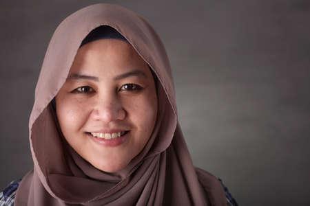 Close-up beeld van mooie gelukkige succes Aziatische moslimdame die hijab glimlachend draagt