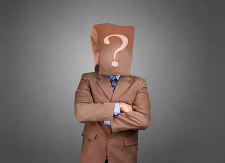 Portrait of businessman in disguise, wearing blank empty paper bag mask covering his face with question mark symbol on it, anonymouse person concept