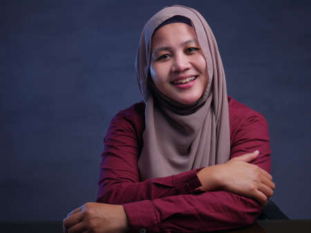 Young Asian muslim businesswoman wearing hijab smiling, cheerful expression. Against dark background. Close up head and shoulders Stok Fotoğraf