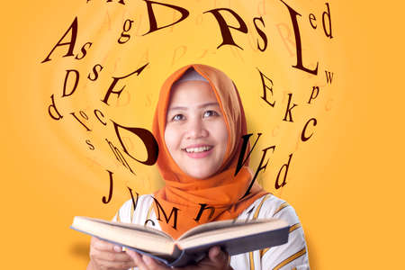 Portrait of beaautiful young Asian muslim woman smiling when reading book, magical book with letters flying from it