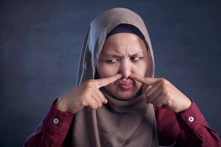 Portrait of cute funny Asian muslim lady wearing hijab close her nose because of bad disgusting smell odor