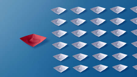 Leadership concept, red origami paper boat leading group of white paper boats on blue background