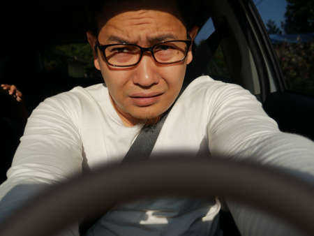 Portrait of Asian male driver get blinded, disturbed dazzled by sun light 스톡 콘텐츠
