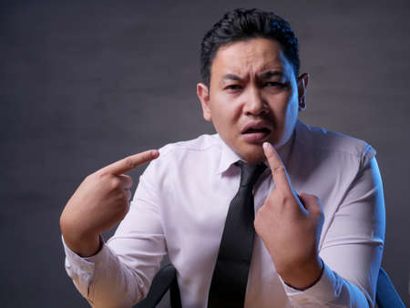 Asian mbusinessman pointing himself with unhappy displeased expression as if he confused to be accused and asking who? me?