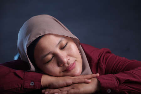 Young Asian businesswoman wearing hijab tired and falling asleep on desk at work, smiling and dreaming expression. Close up head and shoulders against dark background Foto de archivo