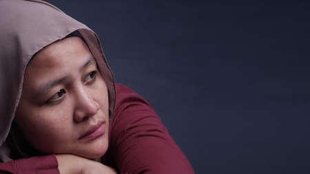 Portrait of sad depressed Asian muslim woman wearing hijab, frustration concept. Sullen hopeless bad emotion. Againt dark blue background
