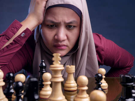 Close up portrait of beautiful Asian muslim woman gets confused when palying chess, business strategy concept