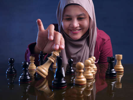 Portrait of beautiful Asian muslim woman smiling happily while playing chess, business strategy concept