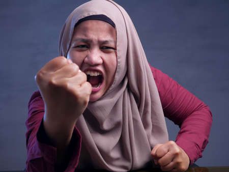 Portrait of mad angry Asian muslim woman shows rude gesture, fist up conflict concept Stockfoto