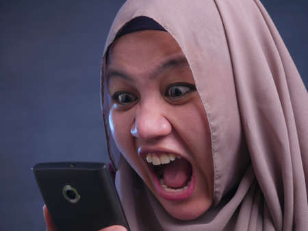 Young Asian muslim businesswoman shows angry expression, having bad news on the phone