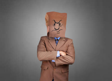 Portrait of businessman covering his face with paper mask with mad angry face drawn on it, furious anonymouse person 스톡 콘텐츠