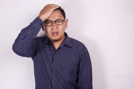 Portrait of young Asian man shows regret gesture, hand on his forehead, isolated on white Stock Photo