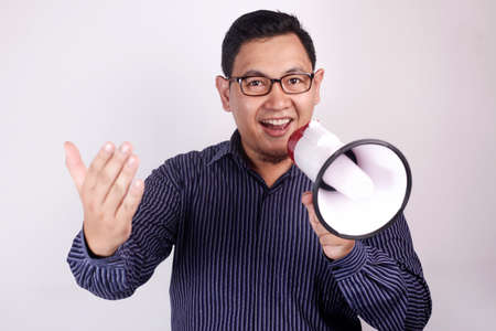 Young Asian man advertisement concept, Smiling expression using megaphone. Close up body portrait over white background