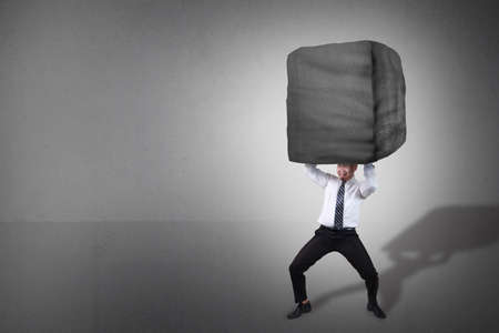 Composite image. Stress overwork and pressure in business concept. Businessman holding heavy stone over his head. Grunge background